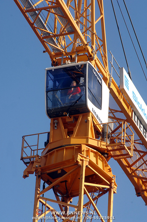 NLD/Huizen/20061109 - Kraanmachinst zittend in zijn cabine wachtend op nadere instructies in de ochtendzon op een bouwplaats in Huizen
