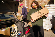 06 NOVEMBER 2020 - DES MOINES, IOWA: A volunteer carries a food box to a client's car during an emergency food distribution at the Iowa State Fairgrounds Friday. A spokesperson for the Food Bank of Iowa said they had enough food for 1,500 families. Each family got frozen chicken legs, frozen liquid eggs, and fresh produce. There will be another emergency food distribution at the Fairgrounds on November 30. Food insecurity in the Des Moines area has skyrocketed since the start of the Coronavirus pandemic. Although unemployment rates in Iowa have fallen since a peak in June, many families that fell behind on rent are now facing eviction. The food bank spokesperson said use of the Food Bank's emergency pantries and distribution points is still increasing.    PHOTO BY JACK KURTZ