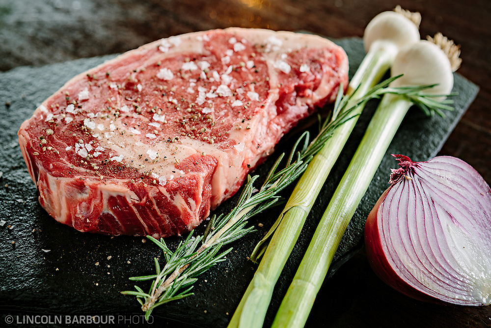 A raw steak seasoned with salt and pepper with rosemary, green and red onions getting ready to be cooked.