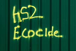 Harefield, UK. 6th April, 2021. Graffiti accusing HS2 Ltd of ecocide is pictured on a security fence around an area alongside the Grand Union Canal cleared of trees and vegetation for the HS2 high-speed rail link. Thousands of trees have already been felled in the Colne Valley where HS2 works will include the construction of a Colne Valley Viaduct across lakes and waterways and electricity pylon relocation.