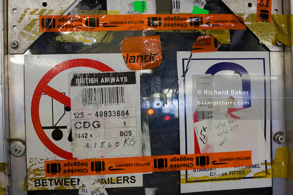 Close-up detail of stickers and dents of a airline baggage container beneath the floors of Heathrow Airport's Terminal 5.