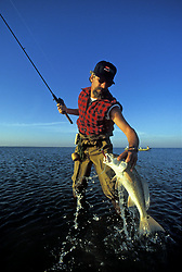 Stock photo of a man landing a redfish in Christmas Bay.