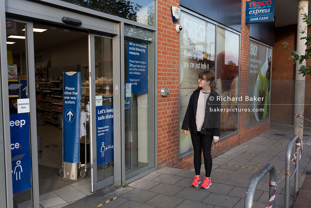 A young woman waits to be directed into a branch of a local Tesco Express supermarket in Herne Hill, during the UK's Conoriavirus pandemic lockdown, on 8th June 2020, in London, England.