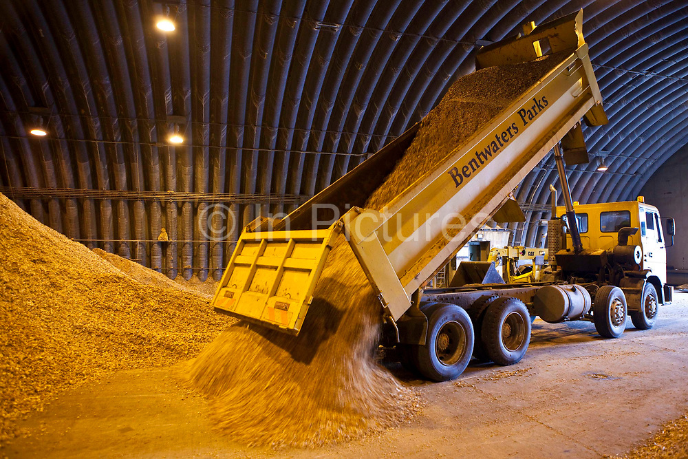 A lorry unloads its cargo of wood chippings in a disused aircraft hanger on an airfield in Suffolk, United Kingdom. There are about 50 tonnes of chippings stored here ready for use in wood chip burning boilers.  This area of the UK is rich in woodland and this wood can provide a sustainable source of heat when used in efficient boilers. This is exactly what local schools are doing thanks to the local council which is managing the resource while supplying wood-fuel for heating. The initiative saves the schools energy, reduces CO2 emissions by 1,200 tonnes a year and cuts their fuel bills by up to 25%.  Suffolk County Council won an Ashden Award for its approach to susatainability.