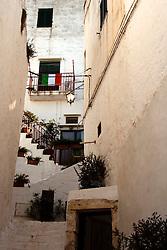 Una bandiera tricolore domina una scalinata del borgo antico di ostuni, nel giorno della partita dei mondiali in cui gioca la squadra nazionale