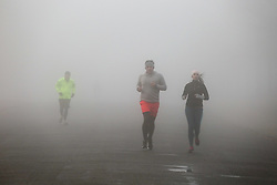 © Licensed to London News Pictures. 08/12/2020. London, UK. Runners in dense fog in Finsbury Park, north London. Freezing cold and foggy weather is forecast across many parts of the UK. The Met Office has issued a yellow weather warning for the UK unlit 11am for low visibility. Photo credit: Dinendra Haria/LNP