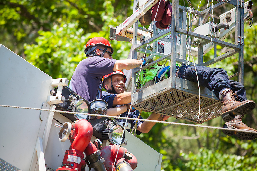 Firefighters Gilbert Monroe, right, and Doug Brede, left, inside Tower 88, remove the worker. Fire department units from Albemarle County Fire Rescue, Crozet and Seminole Trail responded to the area of 3075 Morgantown Road in Ivy for a vehicle fire and special rescue. A bucket truck hit a power line, electrocuting the worker and starting the truck on fire.  Once power was turned off, Tower 88 from Seminole Trail was used to rescue the worker, who was burned.<br /> Photo by Justin Ide