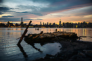 Two girls on a rock in Williamsburg, brooklyn, are taking photos of the Manhattan skyline at sunset.