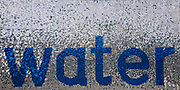 Glittering sign displaying the word 'water'. Blue and silver discs for the word on this hanging display.