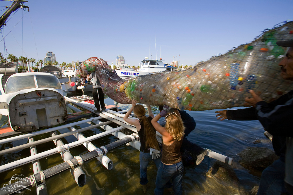 """Adding additional pontoons of plastic bottles to the Junk raft. in the Summer of 2008, the raft called """"Junk""""  will sail 2,100 miles from Los Angeles through the North Pacific Gyre, on raft made of junk. Designed by Dr. Marcus Eriksen and Joel Paschal, the raft, dubbed """"Junk"""" will be constructed from 20,000 plastic bottles, an airplane fuselage, discarded fishing nets, a solar generator, and a bicycle generator. Long Beach, California, USA"""
