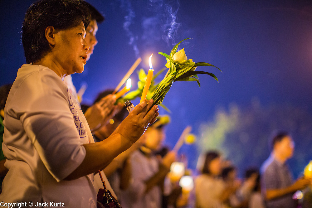 """25 FEBRUARY 2013 - BANGKOK, THAILAND: Thais participate in a candle light procession around Wat Benchamabophit Dusitvanaram (popularly known as either Wat Bencha or the Marble Temple) on Makha Bucha Day. Thais visit temples throughout the Kingdom on Makha Bucha Day to make merit and participate in candle light processions around the temples. Makha Bucha is a Buddhist holiday celebrated in Myanmar (Burma), Thailand, Cambodia and Laos on the full moon day of the third lunar month (February 25 in 2013). The third lunar month is known in Thai is Makha. Bucha is a Thai word meaning """"to venerate"""" or """"to honor"""". Makha Bucha Day is for the veneration of Buddha and his teachings on the full moon day of the third lunar month. Makha Bucha Day marks the day that 1,250 Arahata spontaneously came to see the Buddha. The Buddha in turn laid down the principles his teachings. In Thailand, this teaching has been dubbed the 'Heart of Buddhism'.      PHOTO BY JACK KURTZ"""