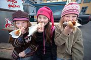 Young Icelandic girls enjoy a famed lambdog at a road side stand in Reykjavik.
