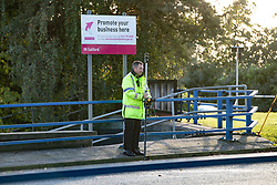 © Licensed to London News Pictures. 27/10/2019. Salford, UK. A police officer surveys the scene . A car lies on its side on a pedestrian walkway at the Pendleton Roundabout on Broad Street in Salford . Members of the public pulled a man and a woman from the wreckage after a BMW car crashed through a barrier and landed on a pedestrian walkway below . Their condition is unknown and police , paramedics and fire crews are at the scene . Photo credit: Joel Goodman/LNP