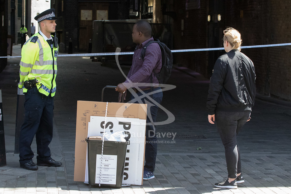 London, June 4th 2017. A man with polling station paraphernalia looks towards the scene during a massive policing operation in the aftermath of the terror attack on London Bridge and Borough Market on the night of June 3rd which left seven people dead and dozens injured