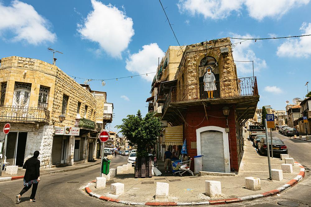 A woman walks down a street in Wadi Nisnas, an Arab neighborhood in the city of Haifa, Northern Israel.