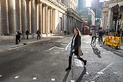 A woman crosses the road in front of the Bank of England in what would normally be the morning rush hour in the City of London on March 17th, 2020. The financial district of the UK is unusually quiet after the government requested people to refrain from all but essential travel and activities yesterday.