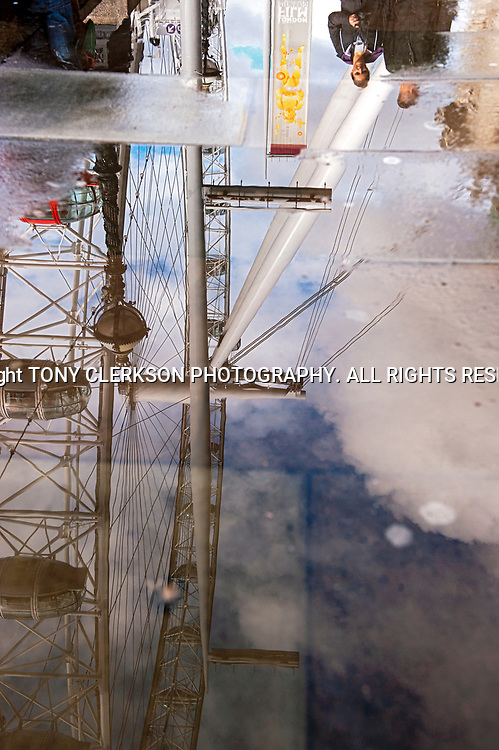 London's Millennium Wheel reflected on the wet ground after a downpour