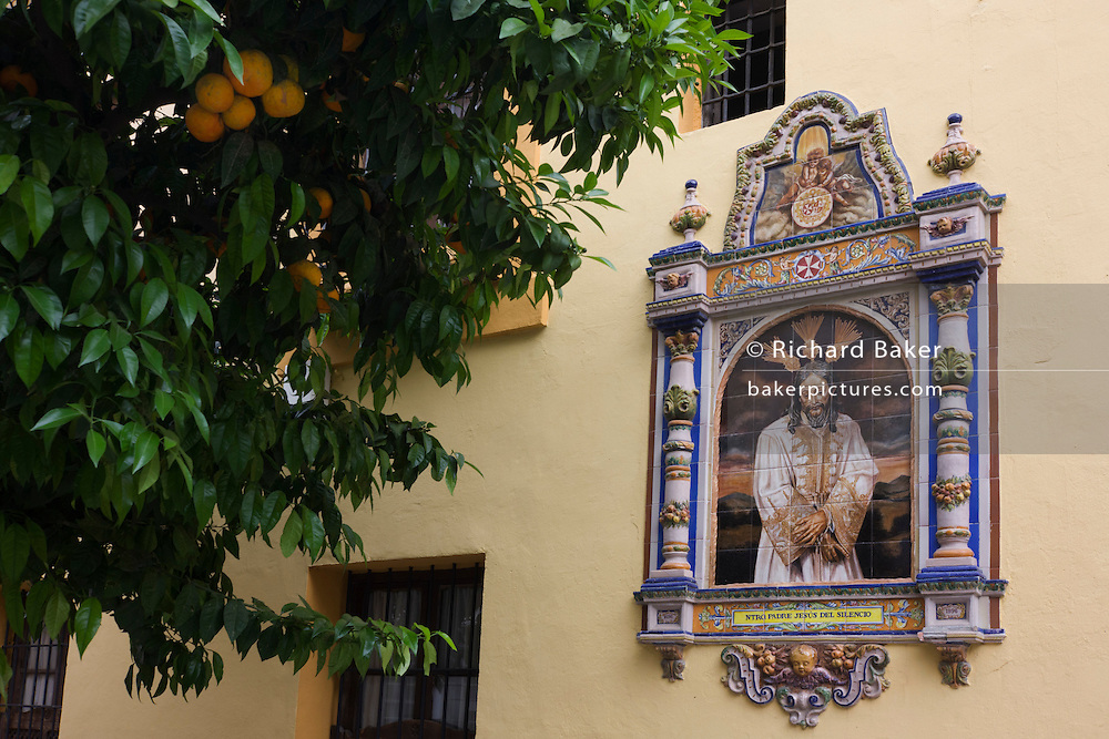 Andalucian ceramic tiling showing Jesus on a church wall in Seville. Beneath the growing Seville oranges that are ripening on their tree in the street below, we see a downbeat Jesus in a gloriously religious context.