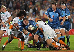PRETORIA, South Africa, 28 May 2011. Dean Greyling of the Bulls is tackled by Coenie Oosthuizen and Ashley Johnson of the Cheetahs during the Super15 Rugby match between the Bulls and the Cheetahs at Loftus Versfeld in Pretoria, South Africa on 28 May 2011..Photographer : Anton de Villiers / SPORTZPICS