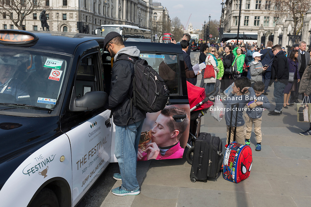 A Muslim family disembark from a black cab and the father pays the taxi fare outside the Houses of Parliament, on 28th March, 2017, in London, England.