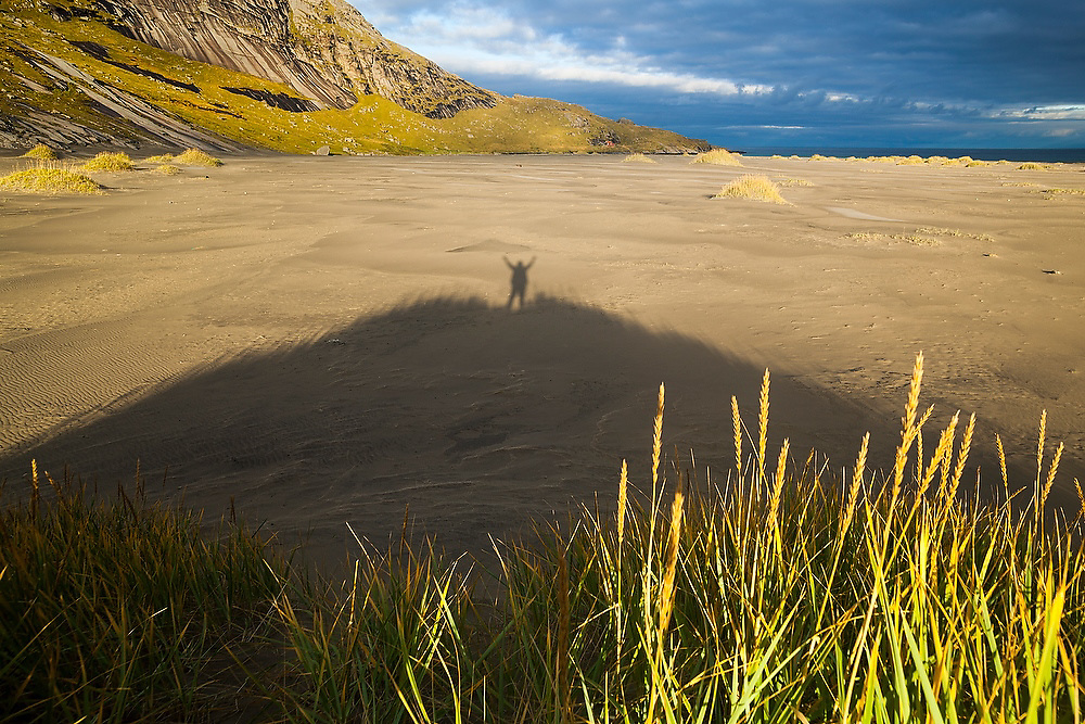 Ethan Welty rejoices at the morning sun on the sand dunes of Bunes Beach, Moskenesoya, Lofoten Islands, Norway.