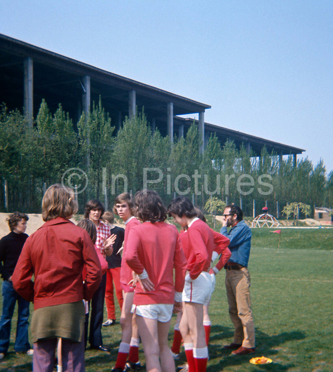 Teenage epat football players listen to their PE teacher during a half-time pep talk during their match at the British School of Brussels in 1975. The players are dressed in red and looking tired on the football field, taken by one of the boy's fathers, an amateur photographer. The picture shows us a memory of nostalgia in an era from the last century.