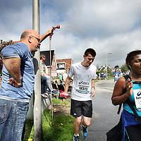 Nederland, Amsterdam , 22 september 2013.<br /> Dam tot Dam loop 2013.<br /> Deelnemers lopen over de Stoombootweg in Amsterdam Noord, aangemoedigd door bewoners.<br /> Op de foto een bewoner van de Stoombootweg zorgt met zijn sproeier voor verkoeling van de deelnemenrs.<br /> Foto:Jean-Pierre Jans