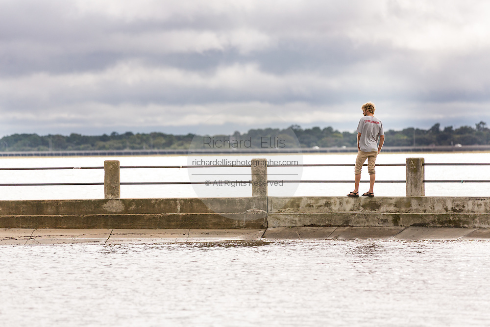 A young man stands on the narrow bulkhead between the harbor and flooded land along Murray Blvd in the historic district after record breaking storms dumped more than two feet of rain on the lowcountry October 5, 2015 in Charleston, South Carolina.