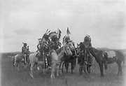 Native Ameerican Indian Dakota men on horseback, one dismounted, 1908. Photograph by Edward Curtis (1868-1952).