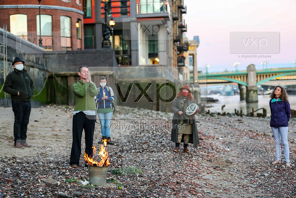 Activists from environmental group XR (Extinction Rebellion) celebrate Low tide hearth fire ceremony on Monday, Aug 31, 2020, by the river Thames opposite South Bank in central London. Participants said that the importance of this 'sacred rebellion' is kindling flames to light up the dark, to illuminate our most essential truths. This is a ceremony which aims to connect and ignite courage for challenges we may not feel prepared for. This is an event which leads into and links with 'Light the Beacons' global sunset event. (VXP Photo/ Vudi Xhymshiti)