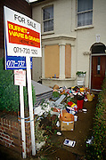 Possessions and rubbish collects outside a repossessed Victorian terraced house in south London. In the foreground we see a For Sale sign strapped on the brick wall by local estate agents Burnet Ware & Graves in Herne Hill, Lambeth SE24. The front bay window has been sealed up with plyboard to stop squatters gaining entrance and the domestic remnants of evicted owners who have perhaps defaulted on their mortgage is thrown on the path - a scene of domestic poverty. As a result of the 1987 a stock market collapse, the UK economy experienced a downturn resulting in public services suffering a reduction, including the loss of owners' homes. The recession of the early 1990s describes the period of economic downturn affecting much of the world in the late 1980s and early 1990s.