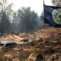 An earth flag on a bamboo pole at the Schindler home on Pine Flat Road somehow survived the inferno as the CZU August Lightning Complex to through Bonny Doon, California. Photographed on Thursday August 20, 2020.