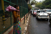 Ram Pyari, 12 waits to sell flowers at a busy crossing next to the flyover where she lives with her family. New Delhi, India