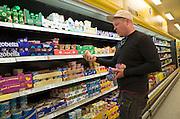 Customer shopping for yogurt in a modern Polish convenience store. Rawa Mazowiecka Central Poland