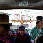 Cholita wrestler Yolanda La Amorosa (right) travels home on a bus with her daughter Adriana after collecting her from school in La Paz, Bolivia. Yolanda is part of the 'Titans of the Ring' wrestling group who perform every  Sunday at El Alto's Multifunctional Centre. Bolivia. The wrestling group includes the fighting Cholitas, a group of Indigenous Female Lucha Libra wrestlers who fight the men as well as each other for just a few dollars appearance money. El Alto, Bolivia, 17th March 2010. Photo Tim Clayton