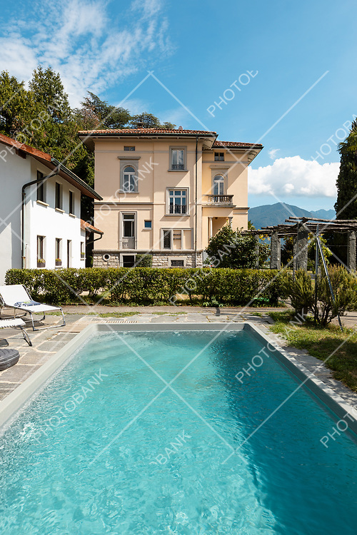 Ancient villa with swimming pool on a sunny summer day. Nobody inside