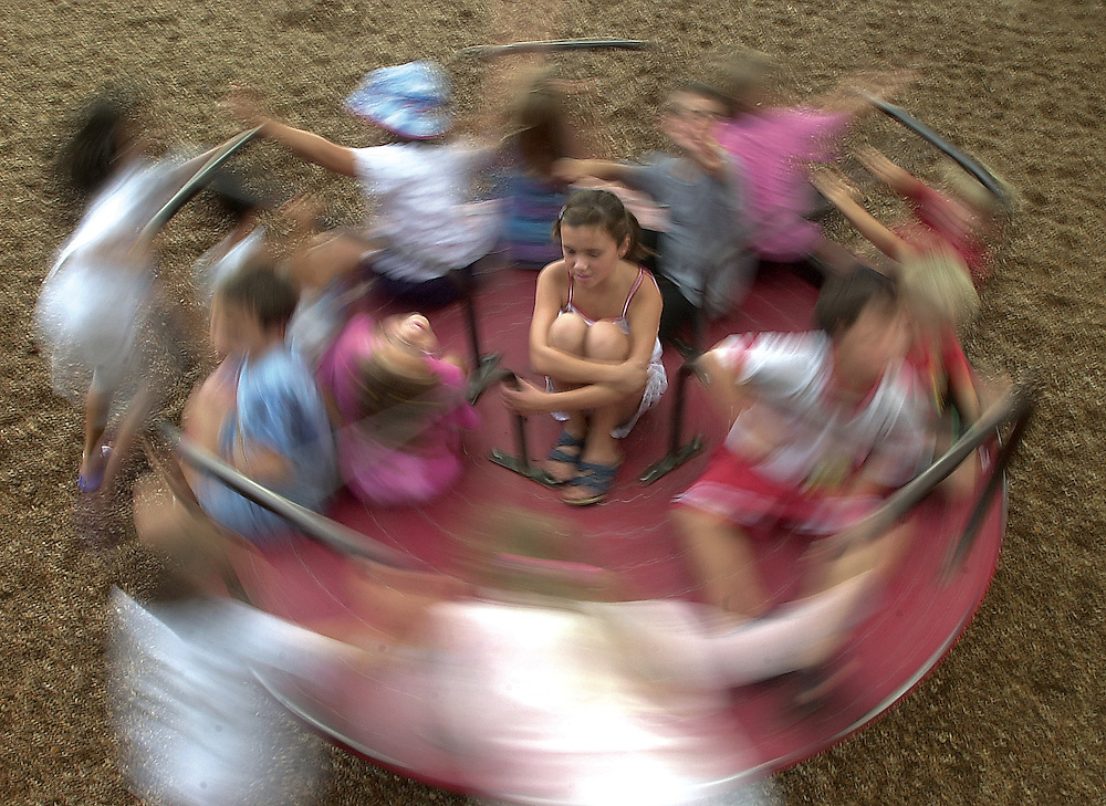 Special education students play on a merry-go-round.