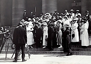 Photograph of National Woman's Party members and Alice Paul gathered with Governor Cox on steps to a building, with photographers and cameras on tripods in the foreground. 1920.