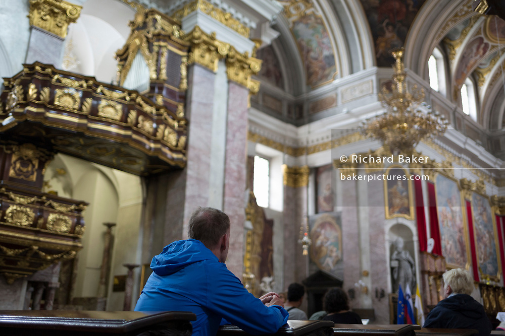 A visitor to the Cathedral of saint Nicholas sits in a pew, in the Slovenian capital, Ljubljana, on 28th June 2018, in Ljubljana, Slovenia.