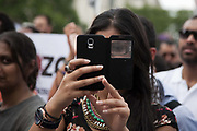 A young woman holds up her mobile phone to record the speeches at Parliament Square and all there is to be seen is her one eye through the cover.<br /> <br /> Tens of thousands of protesters marched in Central London to show their outrage against the Israeli onslaught on Gaza.