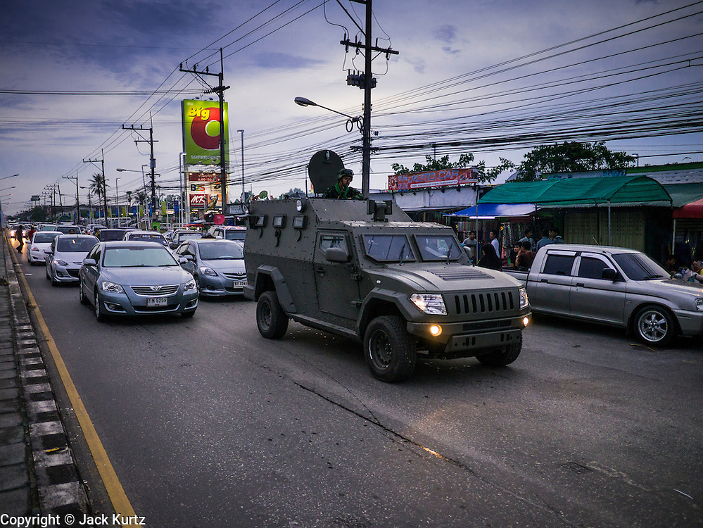 08 JULY 2013 - PATTANI, PATTANI, THAILAND:  A Thai Army armored car patrols along a crowded street busy with late afternoon diners in a Muslim section of Pattani, Thailand, Monday, the day before Ramadan. Ramadan starts July 9 and Monday was the last day observant Muslims were able to eat and drink during daylight hours. Muslims fast during the holy month of Ramadan, taking breakfast before dawn and not eating again until after sunset. The restaurants in Pattani, a Muslim majority city in southern Thailand, were packed Monday afternoon and evening.   PHOTO BY JACK KURTZ