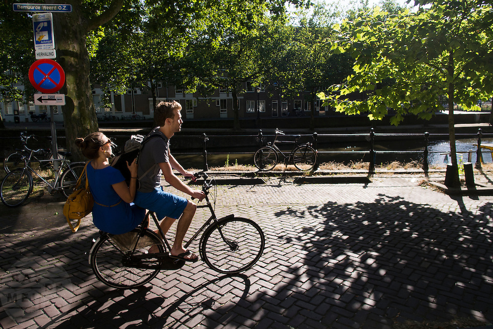 In Utrecht fietst een jongen over de Bemuurde Weerd met een meisje achterop de bagagedrager.<br /> <br /> In Utrecht a man is cycling at the Bemuurde Weerd with a girl at the back of the bike.