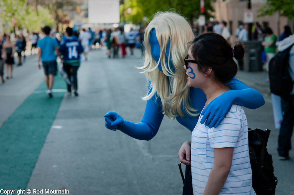 A fan poses for a photo with a 'Blue Man' prior to watching a hockey playoff game. Vancouver, BC