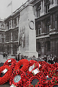 Real remembrance wreaths on the ground at the foot of a black and white vintage era photograph that shows the Cenotaph, currently hiding the real monument being renovated in London's Whitehall.