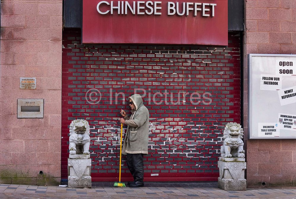 Man sweeping in front of a Chinese resturant closed during the pandemic on 21st April 2021 ib Blackpool, Lancashire, United Kingdom. Blackpool is a large town and seaside resort in the county of Lancashire on the north west coast of England. Blackpool was once a booming resort with it's famous promenade which now, despite having a somewhat shabby appearance, still continues to attract millions of visitors each year. During the coronavirus pandemic however, Blackpool has struggled, with empty streets and closed down businesses creating an atmosphere more like a ghost town.