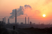 A man rides his motorcycle past a coking factory at sunrise in Linfen, Shanxi Province, China on Thursday, 03 December, 2009. Due to the heavy presence of coal mines and related industries, Linfen was named the world's most polluted city from 2004-2007.