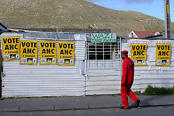 A supporter of the Economic Freedom Fighters (EFF) walks past a shack covered in Vote ANC posters in Masiphumelele near Fish Hoek, Cape Town during the 2016 local government elections held across South Africa on the 3rd August 2016<br /> <br /> Photo by - Ron Gaunt / RealTime Images