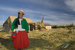Woman outside straw hut on one fo the Uros Islands (also known as Floating Islands or Islas Flotantes), Lake Titicaca, Peru, South America