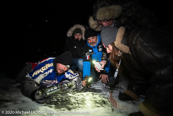 Raphael Bonifay, Simon Pitelet, Frederic Billon, Bertrand Dubet and Bene Zaccherini on the frozen lake to make a Baikal Kiss (drill a hole in the ice and fill it with vodka to drink) during the wrap party after the Baikal Mile Ice Speed Festival. Maksimiha, Siberia, Russia. Saturday, February 29, 2020. Photography ©2020 Michael Lichter.