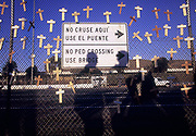 Crosses hung by immigrant rights activists along a fence leading to the San Ysidro, CA pedestrian border crossing represent migrants who have died while attempting to cross into the United States.